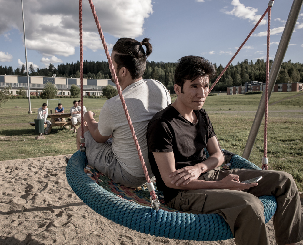 Torpshammar, Sweden, July 5th, 2016. Habib, 23 (right) and Ali 24 (left) play on the swings in the temporary refugee housing complex.