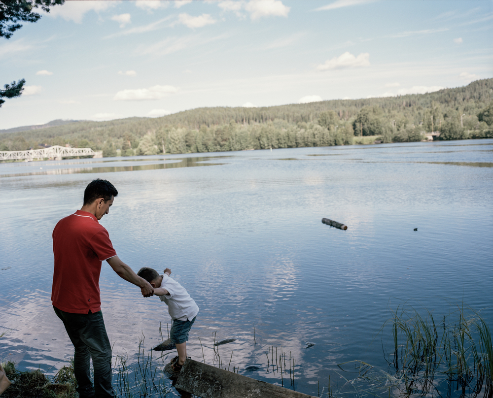 Torpshammar, Sweden. July 5th, 2016. Taha, 3, and his father Mahdi, 28, by the bank of the river 'Ljungan'.
