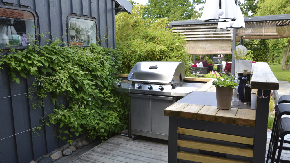 Patio with an American style outdoor kitchen with gas-fired BBQ