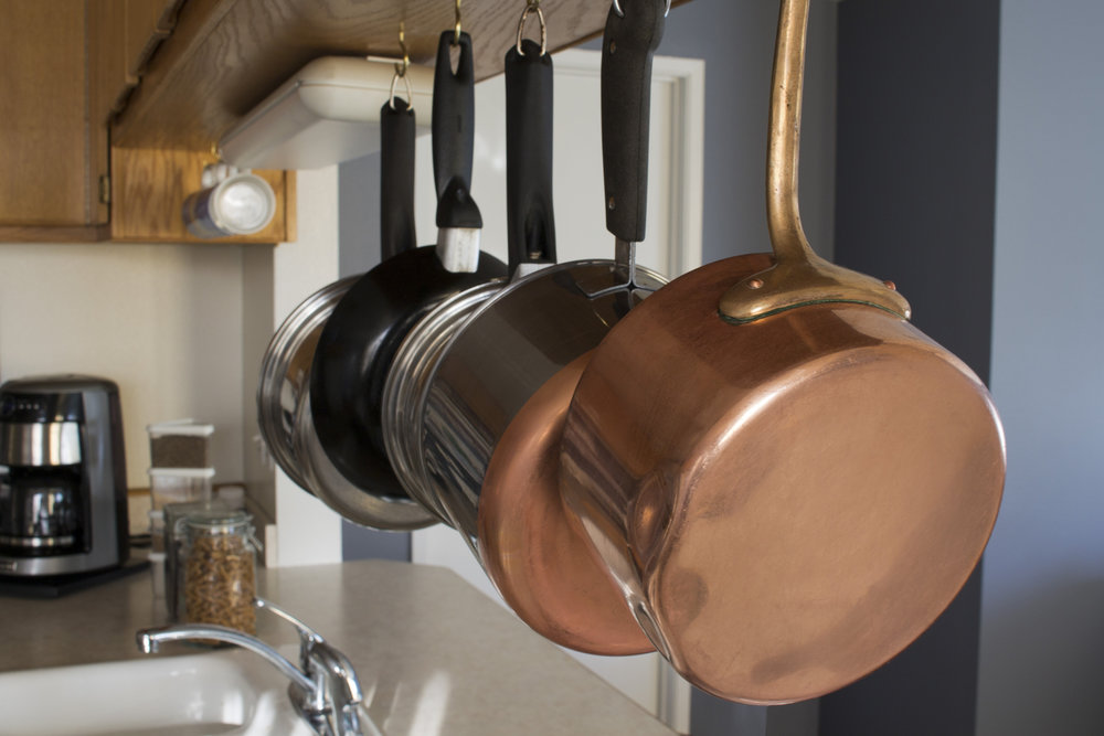 copper pans hanging from rack in kitchen