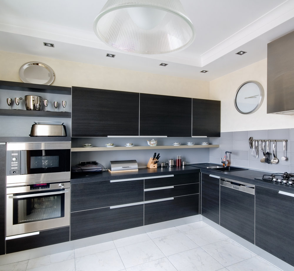 Chic high-end kitchen with fitted cookers, marble floor, and black units.