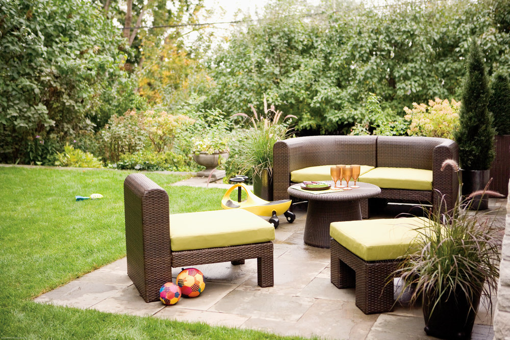 comfy looking, wicker chairs and sofas in a large garden with patio.