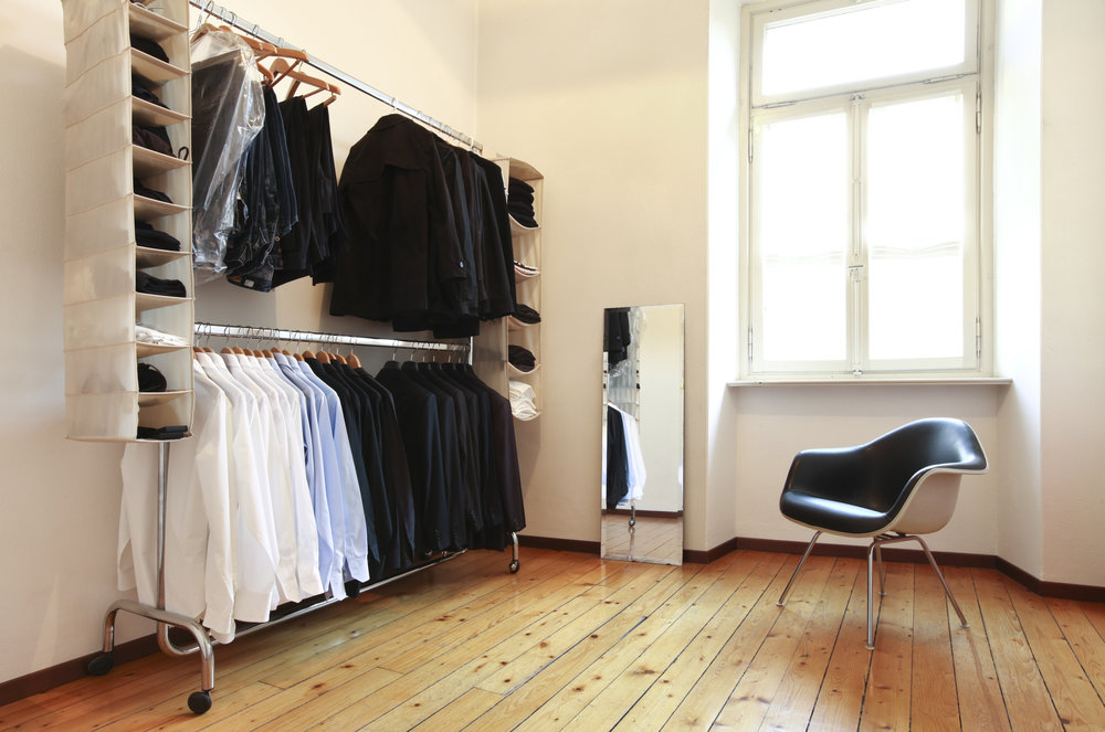 Clothes hanging on rails in a room.