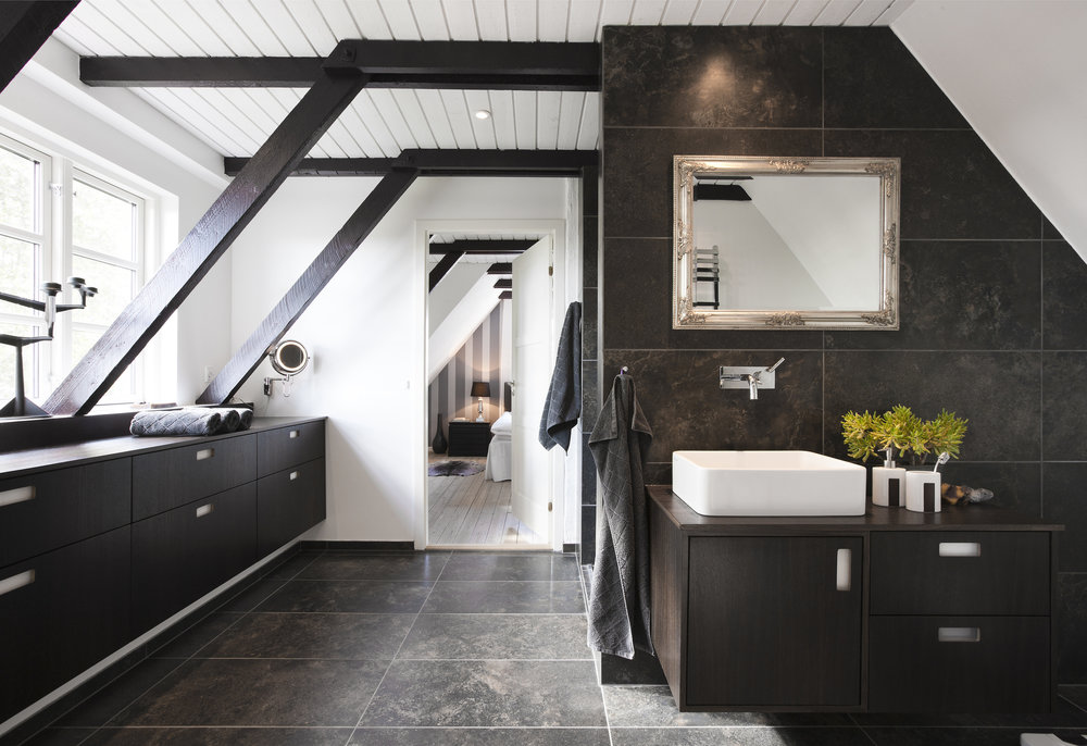 An ensuite bathroom in a loft conversion, with a black and white colour-scheme.