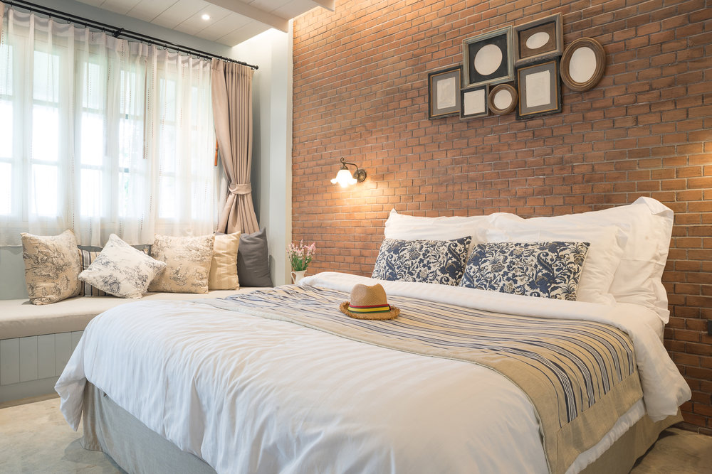 A large bedroom with exposed brick wall.