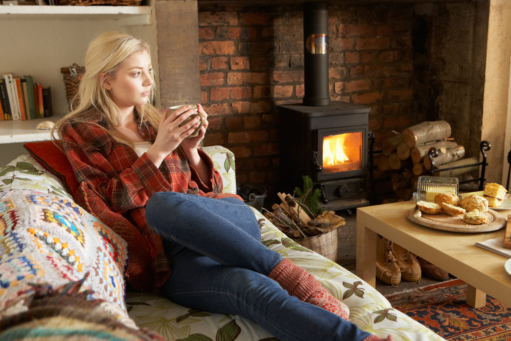 A woman drinking from a mug, in a cosy living room with log burner.