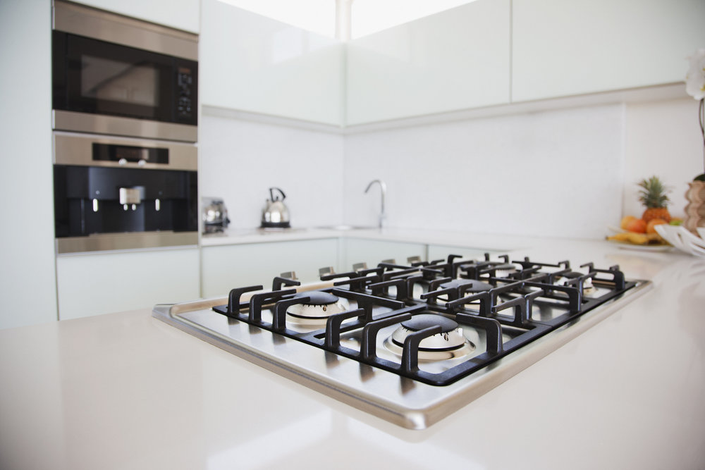Close up of high quality gas hob in galley kitchen.