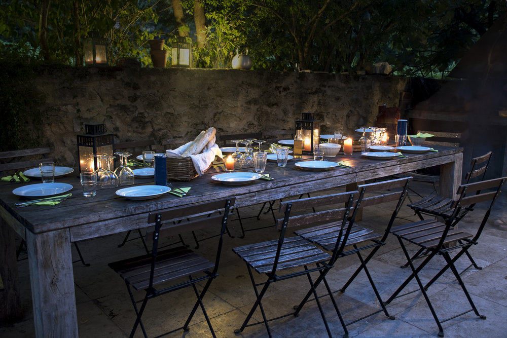 A candle lit table laid out for dinner outdoors on a patio