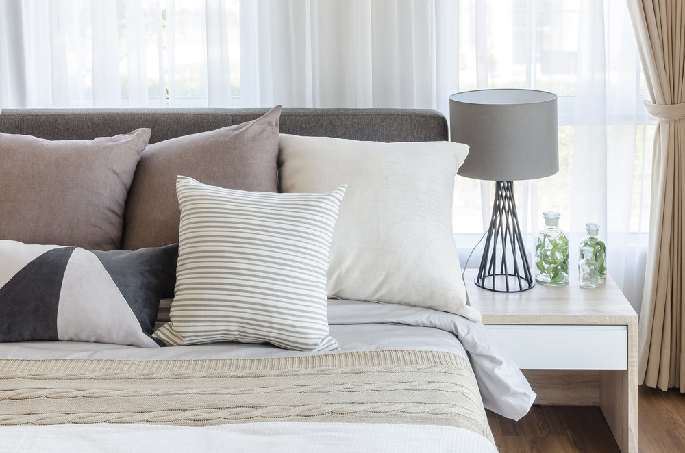 Bed with pillows in a neutral colour-scheme