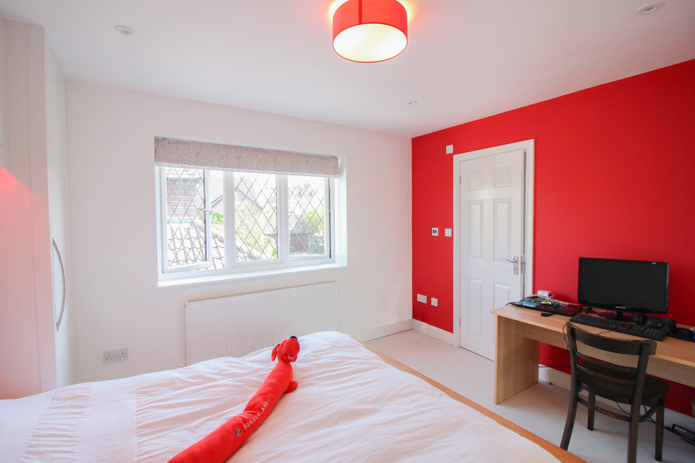 Red Bedding... - What's an en suite without a bedroom? That bold red colour scheme can also be seen in the bedroom's plasterwork. A red and white colour comibination lovingly picked out by a young Sunderland fan.