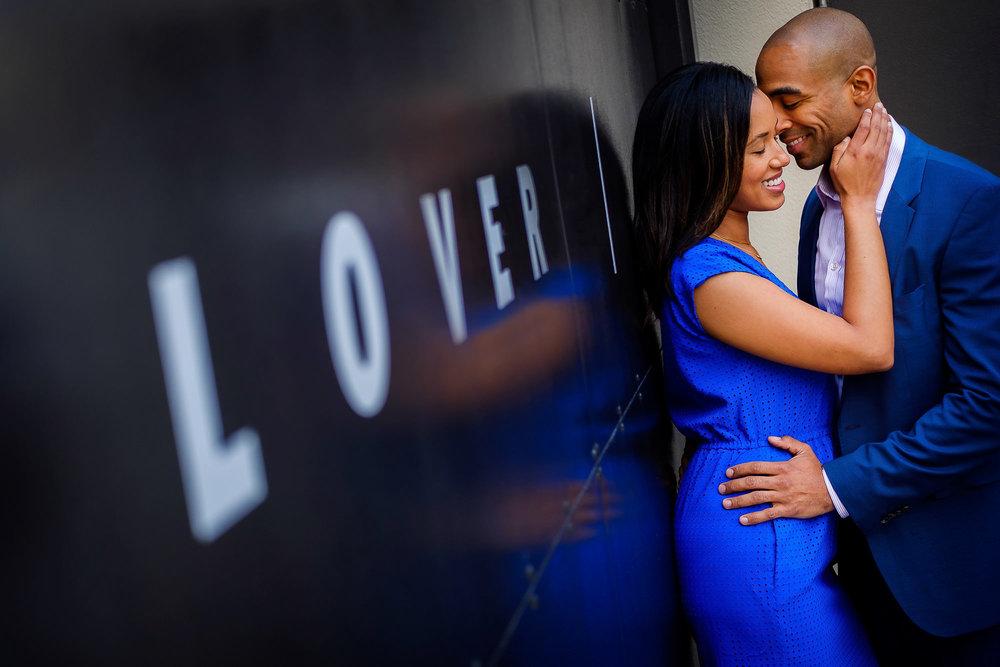 007-christopher-jason-studios-venice-beach-california-engagement-session-african-american-couple-embraces-under-love-sign.jpg