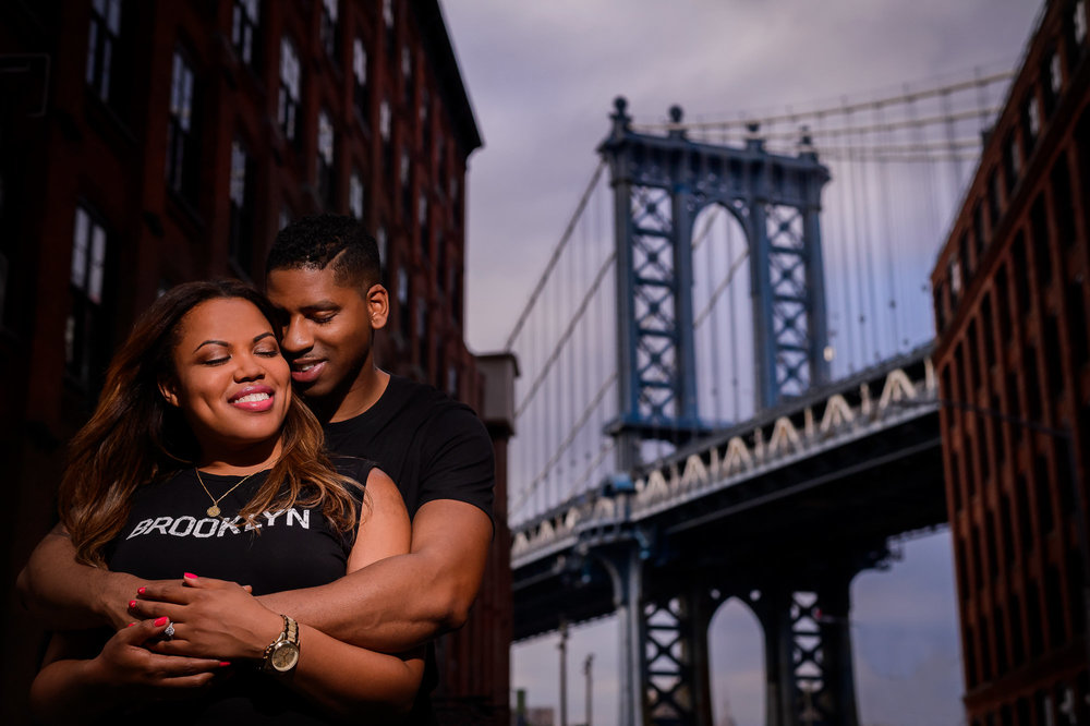 009-christopher-jason-studios-brooklyn-dumbo-new-york-engagement-session-african-american-couple-kisses-in-front-of-brooklyn-bridge.jpg