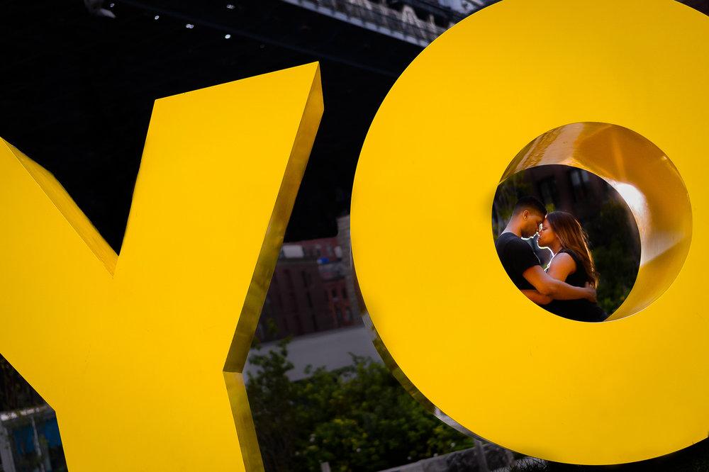011-christopher-jason-studios-brooklyn-dumbo-new-york-engagement-session-african-american-couple-kisses-in-front-of-yo-sign-near-brooklyn-bridge.jpg