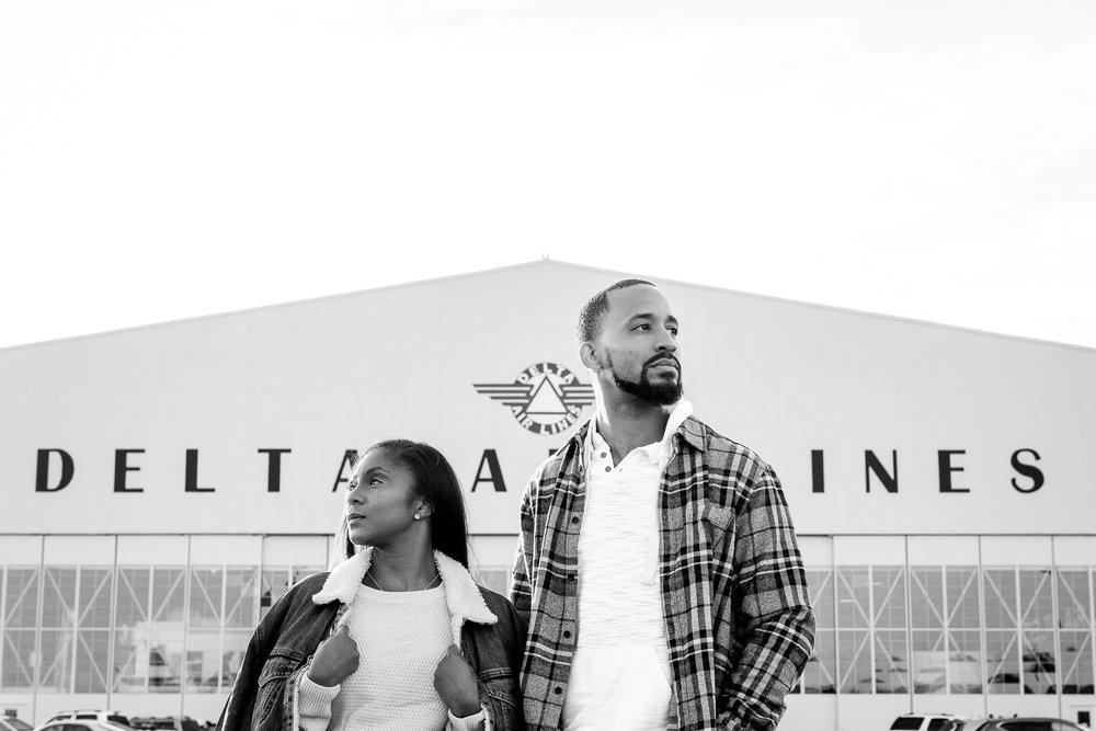 017-christopher-jason-studios-atlanta-georgia-delta-museum-engagement-session-african-american-couple-embraces-next-to-delta-airlines-hanger.jpg