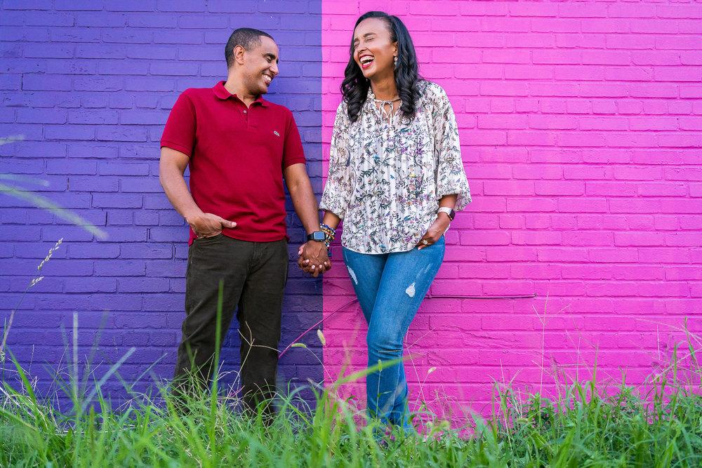 022-christopher-jason-studios-washington-dc-graffiti-wall-engagement-session-ethiopian-eritean-couple-embraces-near-colored-wall.jpg