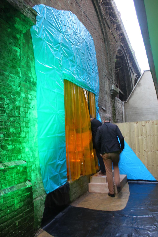 Portal (rail), rubble sacks, rubber flooring, pvc strips, metal railing, Par 64 lights x 2, light gels, 440cm x 280cm x 240cm, 2013