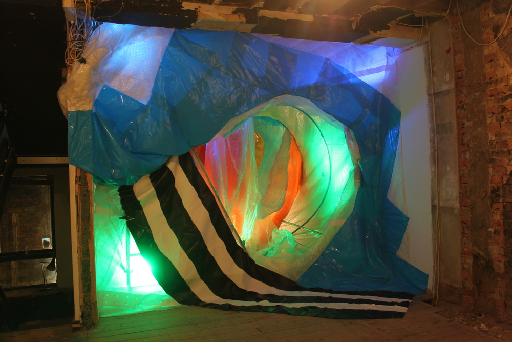 Tunnel (stairs) , polytunnel with cover, scaffold tower, scaffold sheeting, rubble sacks, rubber flooring, clamps, emulsion paint, marker pen, various plastics, light gels, Par 64 lights x 4, floodlight, 300cm x 333cm x 390cm, 2013