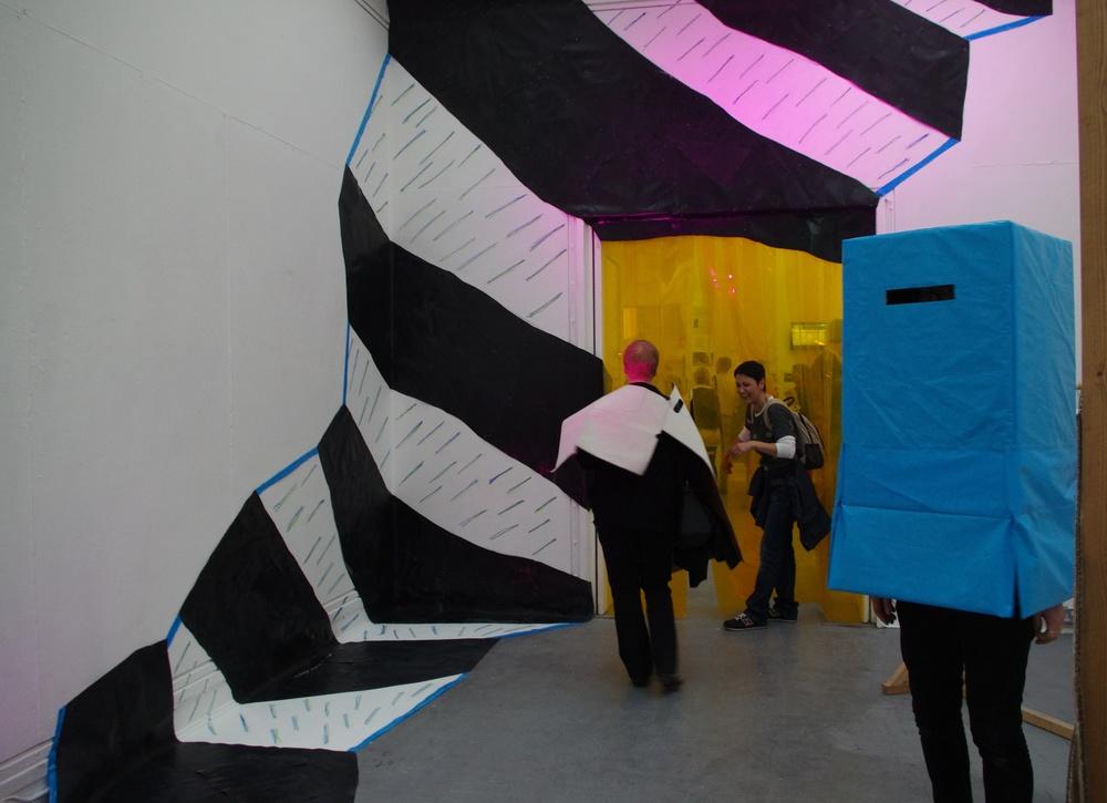 Portal/Staircase (detail), rubble sacks, rubber flooring, marker pen, pvc strips, metal railing, Par 64 light, light gels, 380cm x 300cm x 300cm, 2013