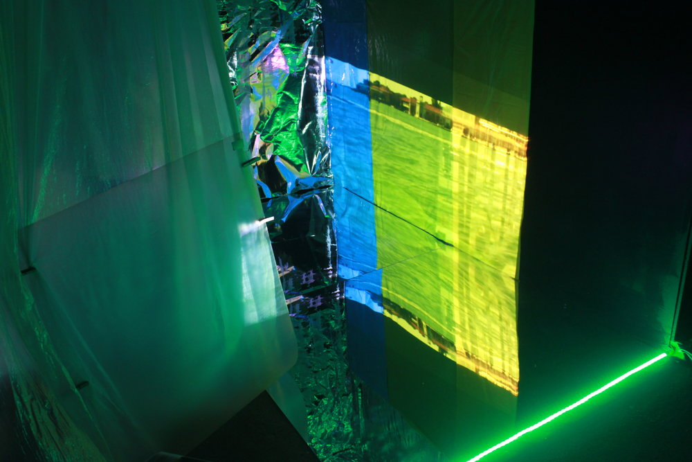 Who's Afraid of Green, Yellow and Blue? (still),  video projections x 2, foil, insulation boards, led lights, circular convex traffic mirror x 2, wooden pegs, tapes, acrylic mirror, various plastics, rubble sacks, 265cm x 236cm x 224cm, 2018