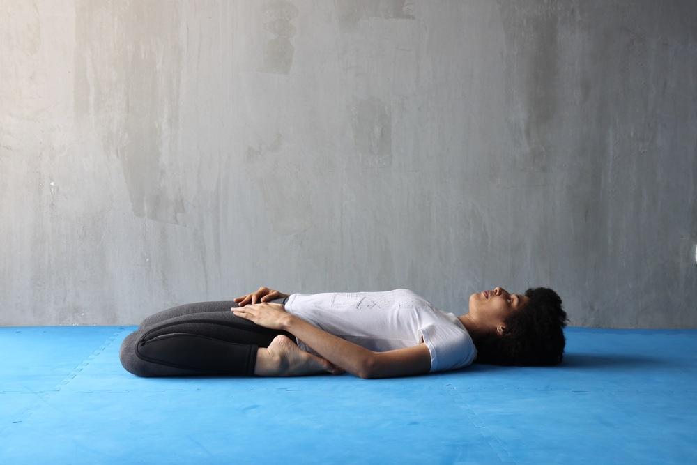 Para finalizar nuestra secuencia, siéntate entre los talones y trata de mantener las rodillas juntas. Intenta ir bajando las caderas gradualmente, ayudándote con las manos para ir bajando despacio. Si te sientes cómodo, puedes inclinar el torso hacía atrás para ir acercando o apoyando la espalda sobre el suelo.