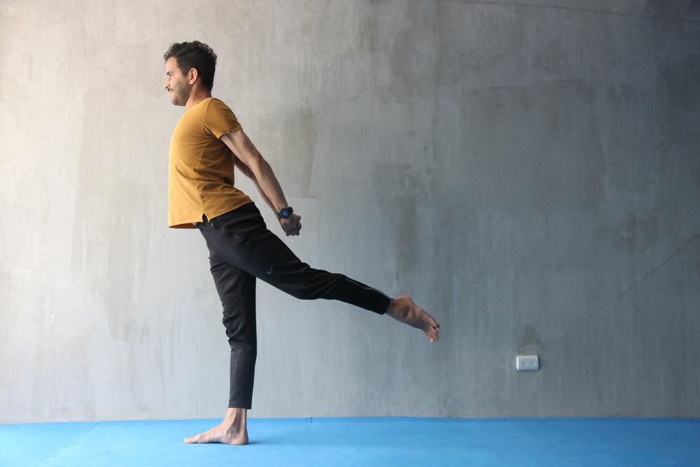 Entrelaza los dedos por detrás de la cintura y aleja tus brazos de la espalda tanto como puedas, proyectando el pecho hacia el frente y llevando los hombros hacia atrás. Mientras alejas los brazos de la espalda, eleva una pierna hacia atrás y permanece algunos instantes tratando de mantener la posición lo más firme y estable que consigas. Compensa, realizando todo hacia el mismo lado. Con eso no sólo fortalecerás la pierna que te sirve de base, también estarás fortaleciendo la musculatura de la espalda y mejorando tu concentración.
