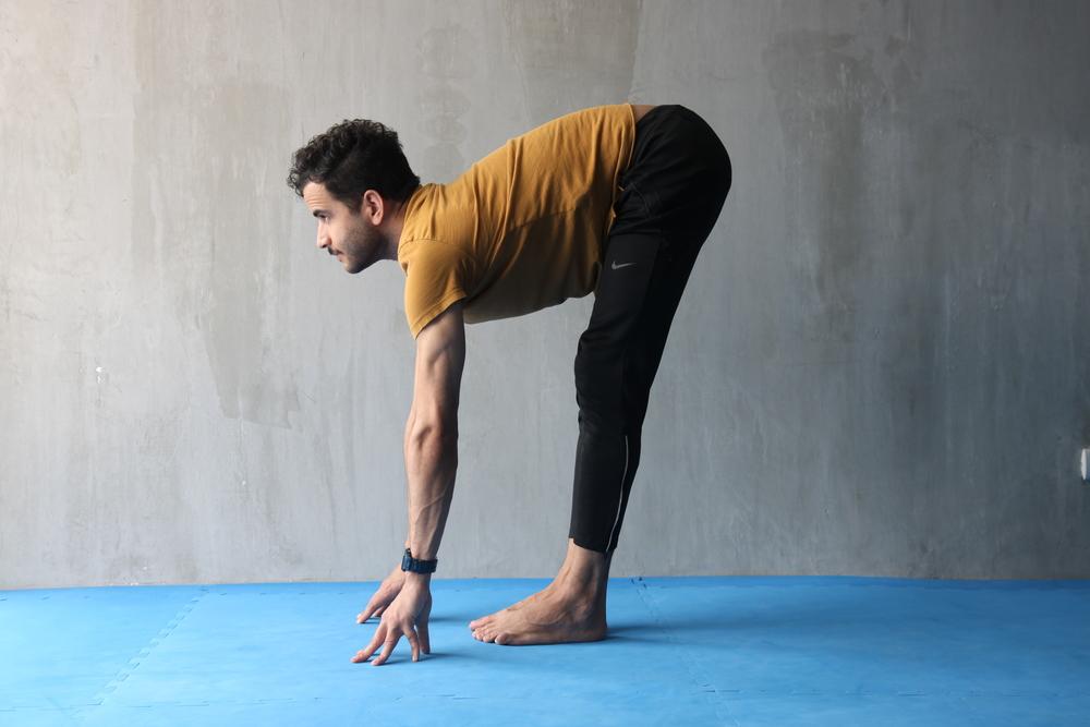 Manteniendo las piernas extendidas, trata de apoyar tus manos en el suelo, sin dejar caer la cabeza. De hecho, trata de bajar intentando proyectar el pecho hacia afuera y manteniendo la mirada hacia el frente.