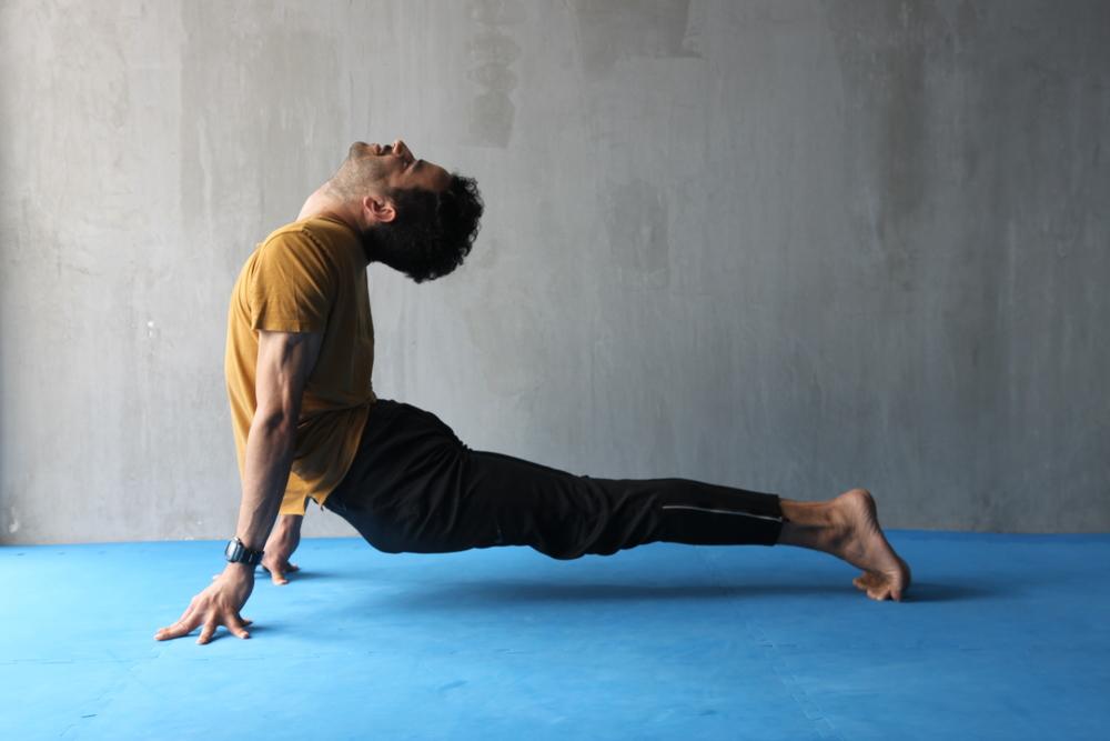 Desde la posición anterior, proyecta las caderas hacia el frente, el pecho hacia arriba y la cabeza hacia atrás. Trata -con cuidado- de que toda la columna se flexione hacia atrás, haciendo que toda la musculatura de la espalda se contraiga y se fortalezca. Al hacer la posición, observa que tus talones se mantengan juntos y tus glúteos contraídos.