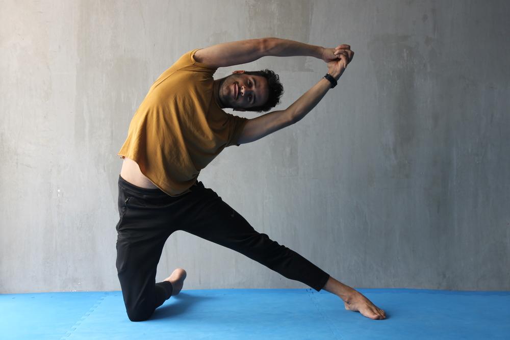 Apoya una rodilla en el suelo y la otra pierna extendida hacia el lado. Al inspirar eleva los brazos y con la exhalación flexiona la columna hacia el lado de la pierna que está extendida. Permanece algunos instantes permitiendo que se distienda la musculatura intercostal y que se vaya fortaleciendo la los oblicuos y el abdomen. Compensa realizando lo mismo hacia ambos lados.