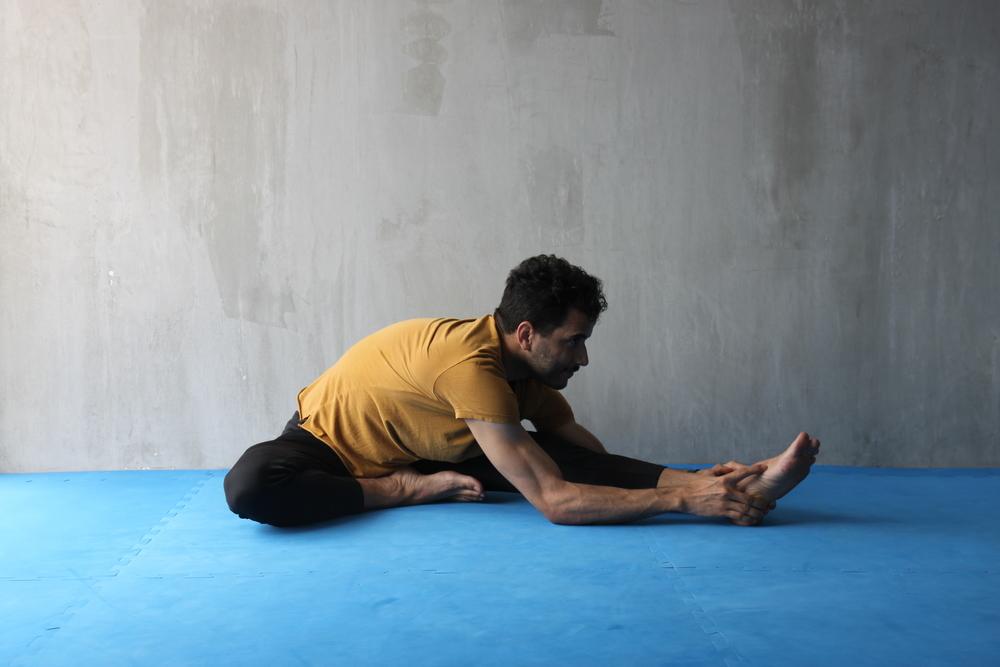 Sentado en el suelo, extiende una pierna y flexiona el tronco sobre ella. Permite que se descontraiga la musculatura de la espalda y trata de involucrar la musculatura abdominal. Intenta bajar desde las caderas, de forma que el pecho y el abdomen se acerquen a la pierna antes que la cabeza. Realiza para ambos lados.
