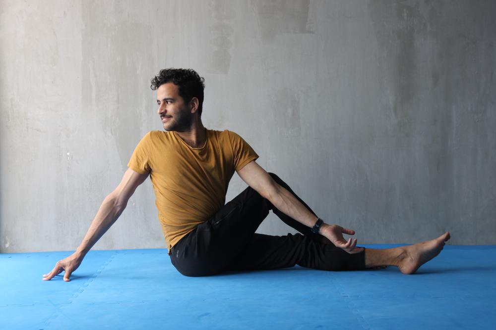 Cruza una pierna sobre la otra y gira el torso hacia la pierna que queda arriba. Con el brazo contrario ve haciendo palanca sobre la pierna para ayudarte a girar más el torso. Apoya la mano de atrás de forma que te ayude a mantener la columna especialmente extendida. Compensa.