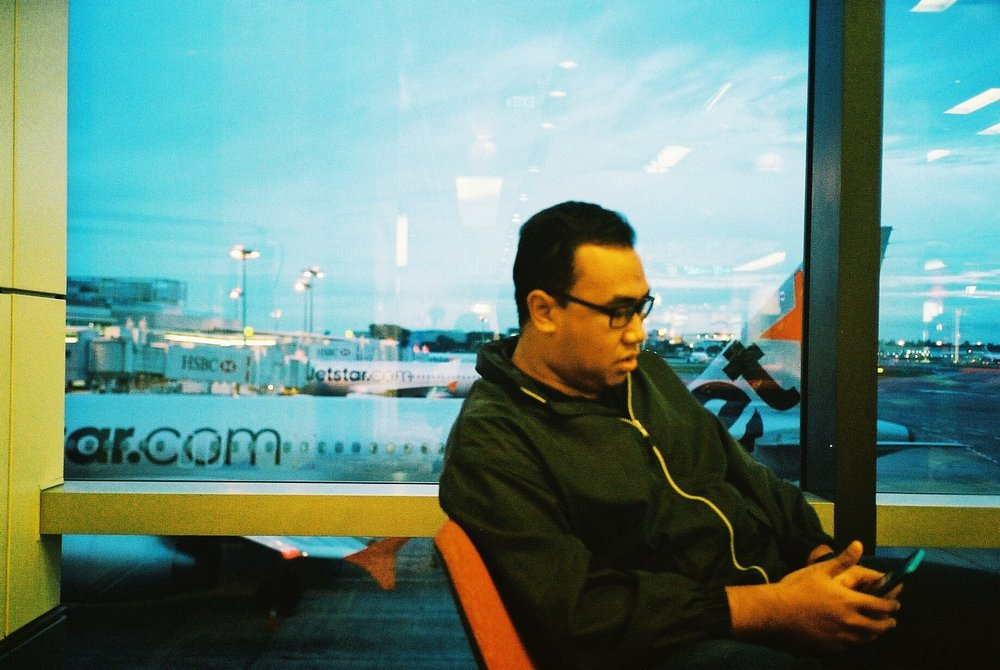 Sleeping at transit, waking up groggy (awoken by Airport Security Officers) and getting ready for the flight. Here though is Amirul.