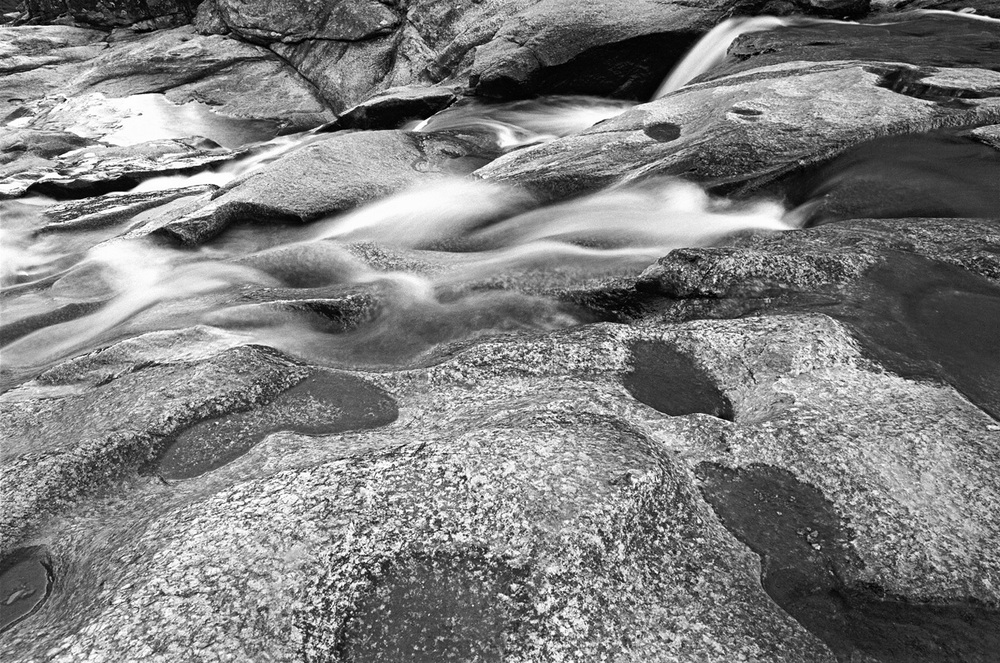 "What exactly is it that I photograph? We had a photographer in today taking pictures of our house (which we're selling), and the agent asked me if I had some good pictures of the building. And, although I've taken plenty of pictures of the house, I don't have any good ones. Why is that? The more I think it about it, the more I realize that what interests me photographically is not so much content as such. Nor is it strictly form either. For me, I now realize it is about atmosphere. The images I like and have most often striven for are evocative, visceral. It doesn't matter so much to me whether the subject is a landscape, or a portrait, or a building. It doesn't matter if it was taken on holiday, as part of a project or just casually walking around in the street. If the photograph is just a picture of something it holds little interest for me. It is when the photograph takes me somewhere apart from the immediate context of its form and content that I get excited about it. I guess this is the same thing as saying that I seek to make photographs which make me, and/or the viewer, feel something. And just why should I/he/she have this sort of reaction to a photograph? Probably because at the moment of exposure I, when presented with the subject, have felt something that has transported my immediate frame of reference to a more profound plane; or else with the resultant picture I discover I've  managed to communicate something that goes a little deeper than the surface representation about either the subject itself, or something more universal. The photograph above was taken back in 1980 at Woolshed Falls, near Beechworth. It is a simple landscape taken with a 24mm wide-angle lens on ""slow"" 25 ISO black and white film, with the camera on a tripod and using a slow shutter speed to further the impression of motion in the flowing water. Voila - form and content. Well so what? None of that is what the picture is about to me. Looking at it over the years I've always been aware within myself of a visceral response to this photograph. I think it goes beyond the nice spread of tones across the picture plane and the acceptable composition. I perceive in this picture a tension that is not there at all in the subject or in the method I used to shoot it. It's almost a presentiment: it is not beyond the bounds of imagination to envision that there seems to be something of a portent in that face-like array of puddles in the foreground quartz. But that may just be me. Other people will see it differently of course - some will like it, others won't. There's no ""getting it"" or chin-stroking about the artist's intent here - how can there be? It is, after all, just my picture that means something to me. Perhaps it's a bit about where I was at that particular time in my life, about to quit my job and head overseas to lose myself for a while. Sure I can think that now, looking back and seeing in context what happened. I don't know, maybe some of that is portended in this picture. Other people can't possibly know all that. I just hope that some of my intent invites viewers to think about the picture a little more deeply and consider why I've bothered to put it in front of them. So I'm thinking, having identified at long last what my pictures are really of, that my next project will be consciously about ""atmosphere"". Just how I'm to go about that I have no idea. But it is an interesting proposition to contemplate: what is it that you take pictures of?"