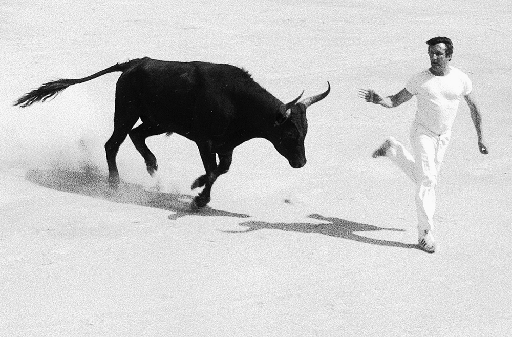 french bullfighting, arles, saturday 21/6/1986 I found a group of FP4 negatives I'd taken in Arles, France back in '86, a couple of years before I had my cameras stolen in Barcelona. The human idiots portrayed carry a multi-bladed razor and the goal is to cut a ribbon tied between the (extremely sharp) horns of a bull. It is, as one would imagine, quite the spectator sport, and thankfully a lot less bloody than the Spanish variety. Still, I'd imagine that from time to time a few of these guys don't end up all that well (not to mention the bulls!). This series is composed of crops from my original negatives. I was using a 70-210mm lens and just shooting from our seats in the stands, so I didn't get quite as close as it seems here, yet I like the crops with their attendant grain and presence. Even though I recall we'd paid extra for seats à l'ombre I remember it being quite hot, which seemed appropriate when I was scanning these yesterday. Forgetting the stupidity of the occasion for a moment, it must be said that it has resulted in the depiction of some quite dance-like and poetic movement. This is for me one of the great joys of photography - the ability to preserve for future delectation the arrested grace of movement and gesture. Even, as here, in the face of certain death or dismemberment.