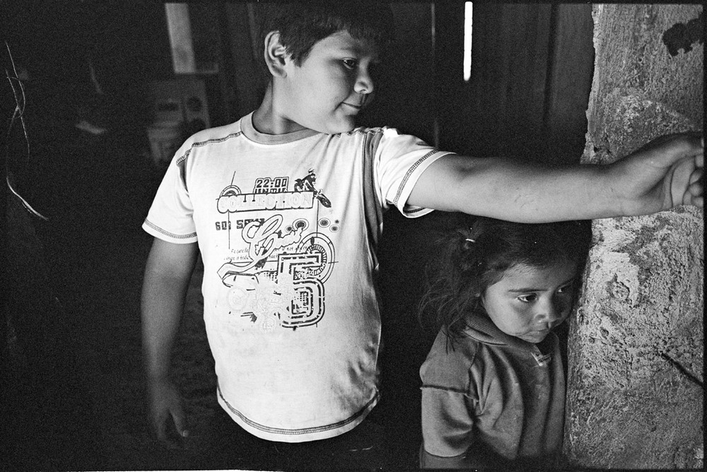 """jarod and jennifer, oaxaca, mexico This is a photograph that I initially scanned in low resolution when I first went through my photos from Mary Ellen's workshop in Mexico. Mary Ellen had highlighted this one on the proof sheet amongst a bunch of similar shots, expressing that it had a nice sense of mystery, as you can't tell what the object of interest is outside of the frame in Jarod's hand (it was a toy aeroplane). I always considered that the photograph could come up a lot better, so today I tracked down the XP2+ negative and tried again. I'm much happier with this scan. There is more detail in the shadows and less of the mushy """"grain clouds"""" that this film gets when underexposed at 400 ISO (the exposure on the two children is fine, but as a result those dark areas are way underexposed, as this was happening in a dark corner of their house). I used the camera and lens I stuck with throughout that workshop, my Leica with its 28mm lens. Recently I've decided that I'm going to commit to really work with the Leicas from now on. I've sold off the Hasselblad system (it was getting ridiculous on my back because of course you always feel you have to take along extra lenses, film backs etc) and ordered a Domke photo backpack that should help me to distribute the weight of the 35mm gear a bit more evenly. The Leicas are, to all intents and purposes,perfect for doing this sort of work, the sort of work I most enjoy, being relatively small,kindof lightweight (I wish they were more so!) and, best of all, virtually silent. Plus I really like that trump-card characteristic of the rangefinder, where you can see what is happening outside of the frame and are therefore able to anticipate what might move into it. Also I really love using the 28mm - this lens has had quite a rest since the workshop, and it is high time it was put to good use again. And, as for the picture, I'd like to think that I will take more photographs of this calibre, getting in close with a wide angle lens, """