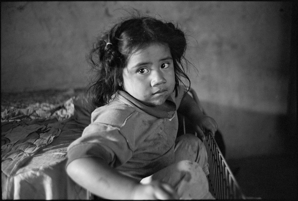 Ashley, Oaxaca, Mexico This portrait dates from March last year when I was fortunate enough to attend a workshop in Mexico with Mary Ellen Mark. Mary Ellen gave me the assignment that day to go out and find a family or someone I could photograph. The taxi I'd taken with another of the attendees, Ari, dropped me in a kind of semi rural spot on the outskirts of Oaxaca which, to be frank, didn't look all that promising. The driver said he was going to have lunch and would be back in a couple of hours. Ah, siesta! So, here I was kind of wandering down this dirt road wondering how I was going to fill in the hot afternoon when a couple of kids walked by. I raised the camera to take a quick shot and the elder of the two, a boy of about 9 or 10, said to come with them to their home and take their photos there (well, I think that's what he said, as there was a distinct language barrier). Now this wouldn't even be a consideration in Australia. No way. But I'd already learned that Mexico is a whole lot less uptight and hysterical about these things, and prefers to think the best of people rather than the worst, so I felt comfortable enough. Besides which, I didn't have the impression there would be too much else on offer to photograph otherwise. They just lived a couple of hundred metres away, and (reassuringly) mama and papa were both home. The family is just wonderful. Mama (Mayra) had just prepared lunch so there was delicious home-made tamales and watermelon. There were five children, including the little girl from next door, who were all really quite far from camera shy and, collectively, in possession of a totally infectious sense of fun and laughter. Needless to say I spent the most wonderful couple of hours that day, despite the absence of a common language, and as a bonus got lots of nice pictures. This one is from the second day I went out there (with Mary Ellen's encouragement I went back three times, both to take pictures and to give them copies of the pictures I'd taken the previous time). That second time I also asked Leslie along, another of the workshop participants who was at a bit of a loose end with no plans for the day, and it was even more fun with two of us crazy gringos (or whatever) snapping away. Ashley, the youngest of the children, plonked herself in a shopping trolley in the single room all the children shared and I got this shot, which I like a lot. It is interesting to compare it with Leslie's shots which are colour and show the red of the top Ashley was wearing. I know Leslie went back to them earlier this year, and Mary Ellen rang Leslie from this summer's workshop in the past month or so to ask for their address so that another photographer could go. So the family home has become a favourite destination for Mary Ellen's students! It is rare, yet truly satisfying when things work out well from a start of seemingly not much potential. In this particular case, the experience has furnished me with one of my most intense lessons yet in reaffirming to me what is so great about photography.