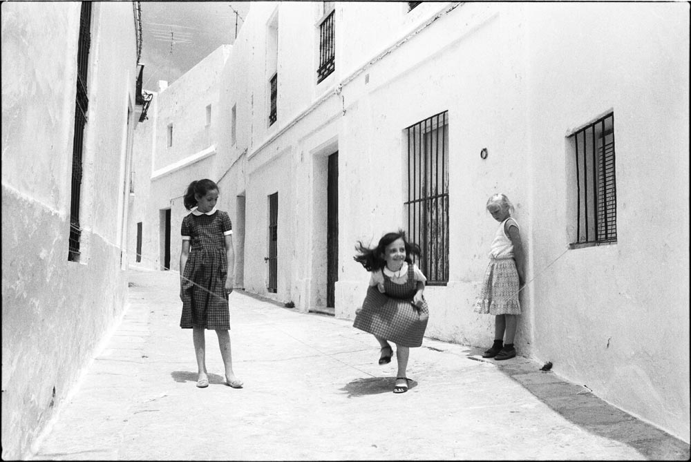 skipping girls, pueblos blancos, spain hidden treasures While looking back on your old negative files or old digital files do you ever find lost gems that you then wonder why you hadn't seen them in the first (or second, or nth) place? For me, this is one such photo. On the proof sheet it looks, quite frankly, muddy and boring, so I always skimmed over it. Of course this may well be because I tended to think of proof sheets as a necessary evil, and didn't take too much care with them. But last time I was looking through, searching for something else, it struck me that this particular frame was probably worth a closer look. And this little swan emerged from an ugly duckling. I guess sometimes it takes time and quite a few views to see some of the ones that don't shout out to you at first. Maybe when we are too close to the experience of shooting we tend to dismiss some shots or blocks of shots as not being as good as something that came a bit later, or we just diss it out-of-hand because it doesn't look any good as a tiny proof. Anyway, I'm glad I found this one, albeit belatedly. It now goes in my portfolio of best shots, and people seem to like it. So, in fact, this makes it for me a long-lost treasure.