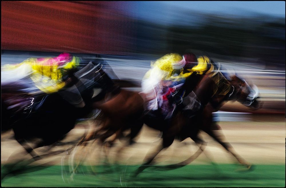I'm not a fan of horse racing, but I have to admit it IS colourful, and it allows ample scope for some photographic tricks like nice blur. The ability to show the passage of time as a fixed moment consisting of motion blur - for photography, it's a one-horse race. Of course the passing of time can be suggested in other ways with different art forms - dance, for one, and music and cinema, but not in the same way as photography. With a picture such as this one, the contiguous moments are unravelled into one moment, so that the passage of time is indicated as one entity, not as a continuous flow. Perhaps the above isn't clear, but I think I understand what the hell I'm on about. But then again I wouldn't bet on it…