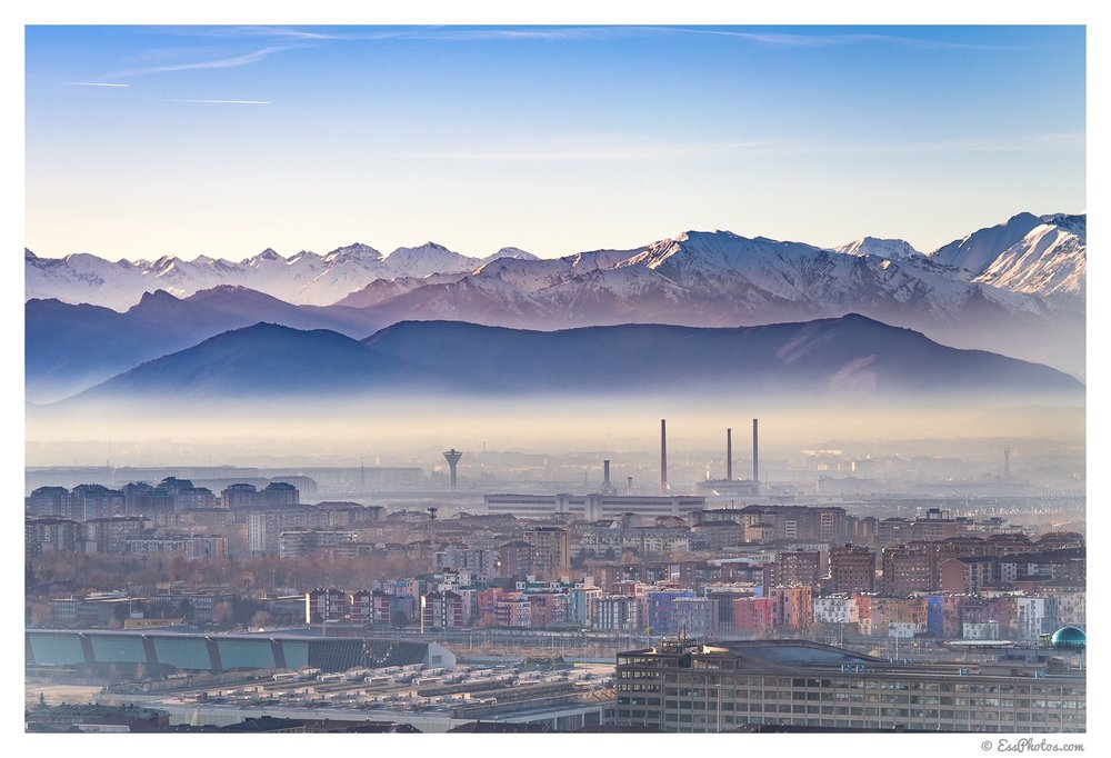 From front to back: Lingotto, Olympic Village, Mirafiori, a LOT of smog, and the Alps. 85mm, 1/320, f/8, ISO 100. Shot on a full-frame camera.