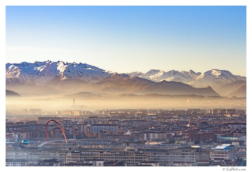 From front to back: Lingotto, Olympic Arch, a LOT of smog, and the Alps. 85mm, 1/320, f/8, ISO 100. Shot on a full-frame camera.