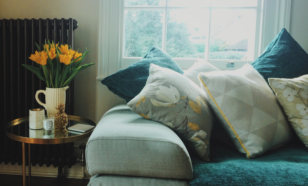My living room in Spring. Patterned cushions from a selection at John Lewis and Tesco. Art deco side table by Zara Home. Gold pineapple by Rockett st George. Marble tea light holder by Conran for M&S. Cream jug by Aromaround.