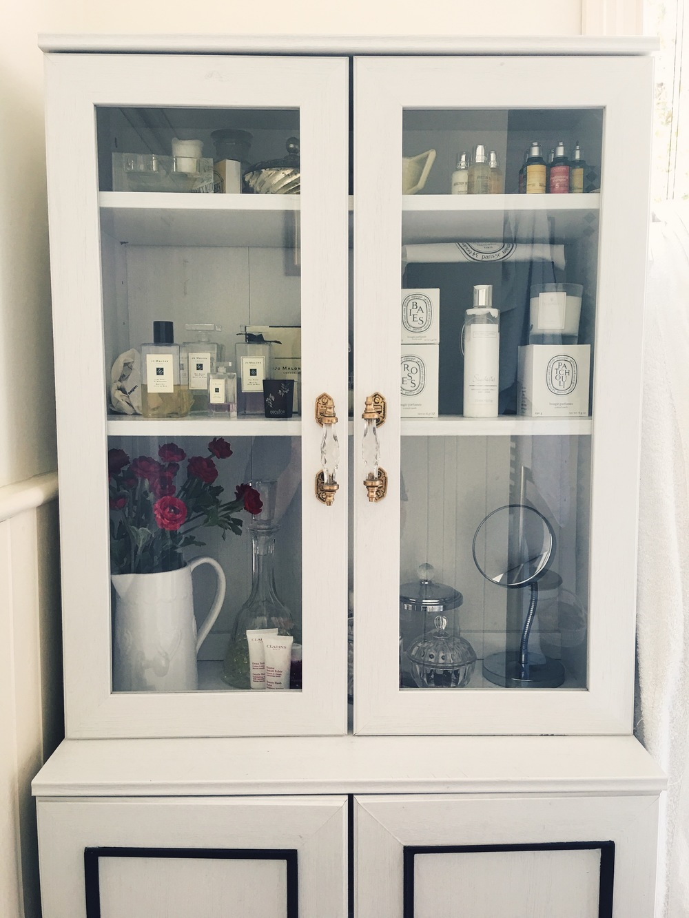 This display cabinet is from Ikea. I added handles from notonthehighstreet.com, and mouldings on the bottom two doors which I painted black to give it a more glam monchrome look. The display area reveals decorative and luxury bathroom items, and the hidden area contains the stuff I do not want on display like cleaning products. tampons and rubber ducks!