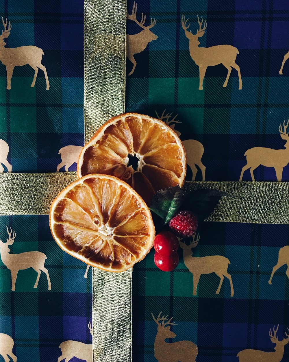 This tartan deer wrapping paper is by M&S. The gold ribbon and faux berries are by Hobbycraft.