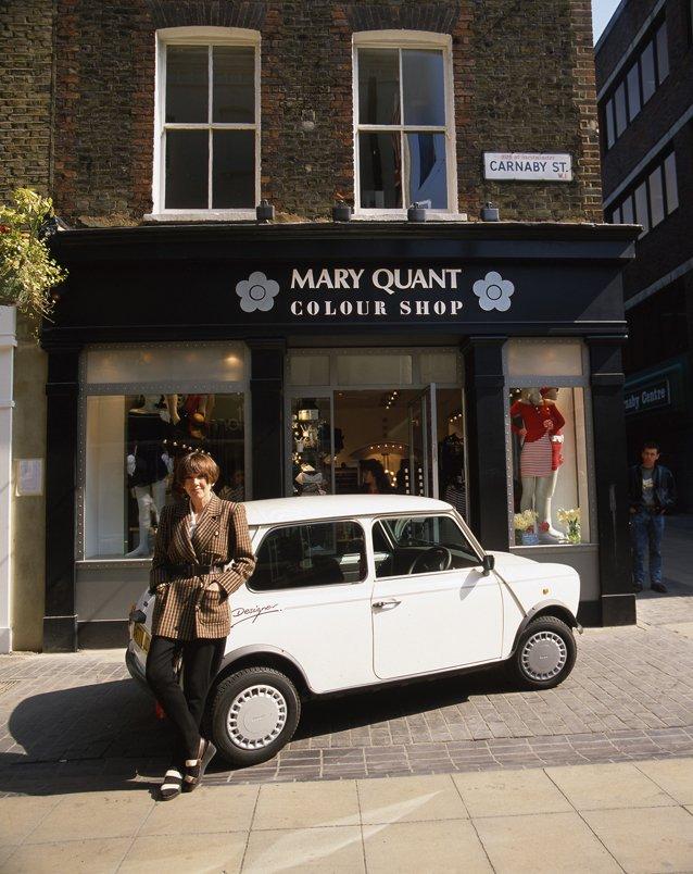 Mary Quant posant avec la Mini-Cooper qu'elle a conçue en 1988 devant l'un de ses magasins.