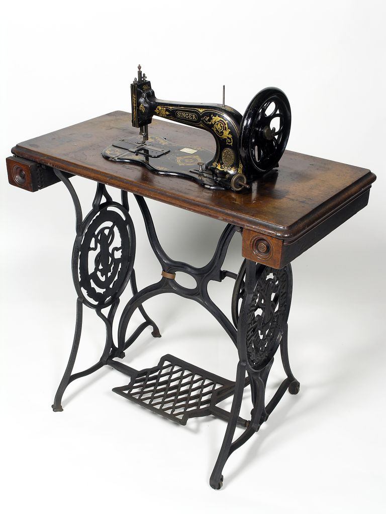 Une machine Singer et sa table de travail avec tiroirs.