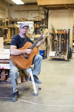 Will Nash plays one of his acoustic guitars in his workshop.