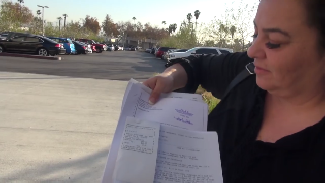 Claudia Ackley holding paperwork filed with the California court system.