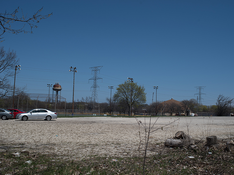 Facing north across the lot towards another ballpark with stadium lights.