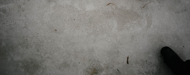 A track found on the Dufield Pond driveway. It was elongated, and appeared to have articulated toes. There were many boot prints in this area, and it is difficult to tell if this is a mundane print misshapen by the melting of ice and snow. Investigator Tobias Wayland's size 12 boot is in the lower right of the photograph for scale.  (Emily Wayland / Singular Fortean Society)