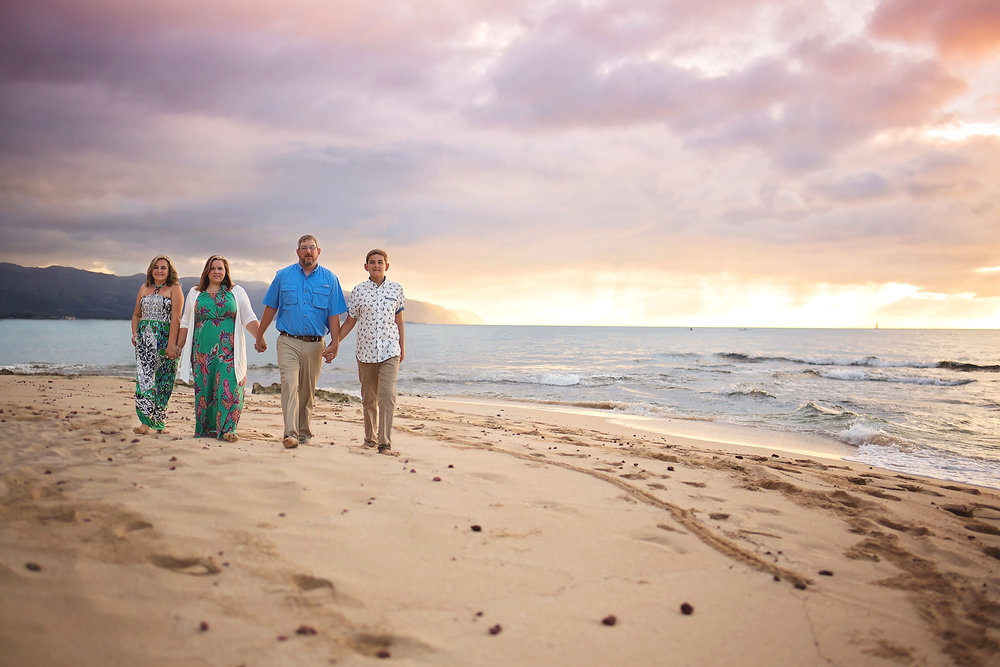 Family of 4 holding hands looking at the camera as they walk in a line along the beach at sunset.