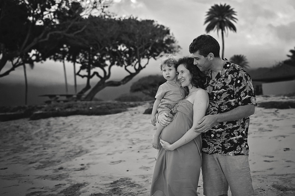Black and white photo of a family of 3 standing on a beach looking out off into the distance. Kaneohe, Oahu, Hawaii.